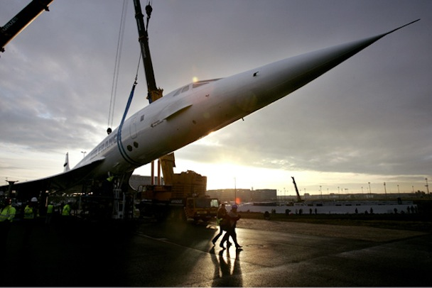 The retired Air France Concorde number five is prepared by employees to be lowered by cranes onto py..