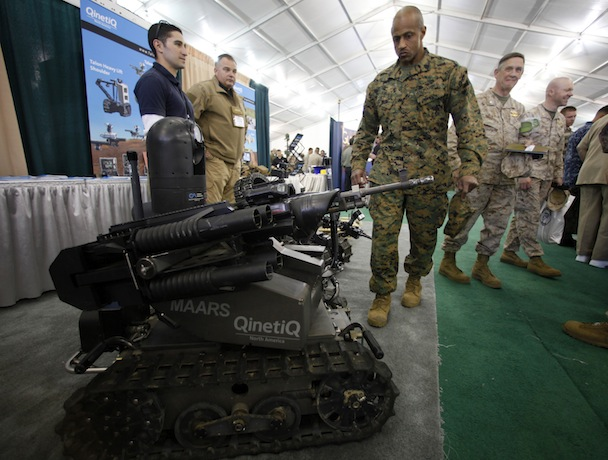 A soldier looks at a MAARS robot at the Marine West Military Expo at Camp Pendleton, California