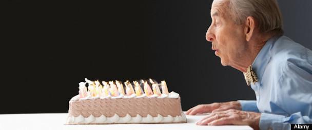 Senior Hispanic man blowing out birthday candles