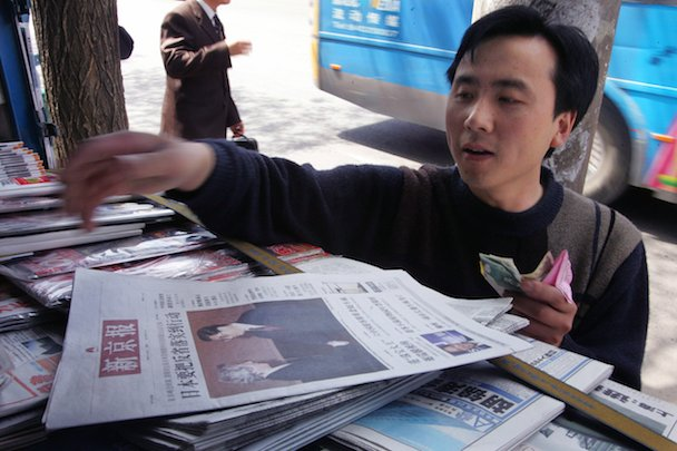 A Chinese man buys an issue of The Beijing News at a newsstand in Beijing.