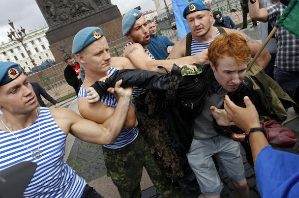 Former Russian paratroopers shove gay rights activist Kirill Kalugin aside to stop his one-man protest in St. Petersburg