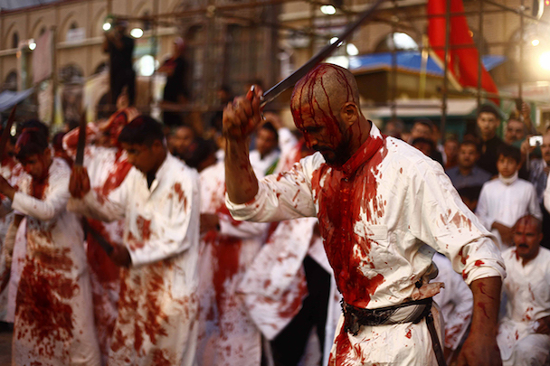 Iraq Shi'ite Muslim men bleed as they gash their foreheads with swords and beat themselves during the religious festival of Ashura in Najaf